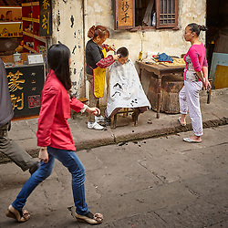 A mother gives her young son a haircut on the street in front of their house as tourists pass by in Old Chongqing, Southern China
