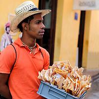 Central America, Cuba, Havana. Cuban vendor sells crispy cinammon tortilla chips on the street in Old Havana.