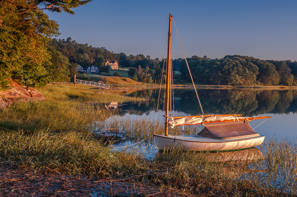 Catboat in strong first light along shoreline, distant homes and dock, Freeport, ME