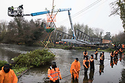 HS2 security guards form a line across the River Colne in front of Dan Hooper, widely known as Swampy during the 1990s, and a large cherry picker containing a bailiff on 8th December 2020 in Denham, United Kingdom. The climate and roads activist had occupied a bamboo tripod positioned in the river the previous day in order to delay the building of a bridge as part of works for the controversial HS2 high-speed rail link and a large security operation involving officers from at least three police forces, National Eviction Team enforcement agents and HS2 security guards was put in place to facilitate his removal.