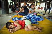 """23 MARCH 2013 - NAKHON CHAI SI, NAKHON PATHOM, THAILAND:  A child sleeps in a common area before the tattoo festival at Wat Bang Phra. Wat Bang Phra is the best known """"Sak Yant"""" tattoo temple in Thailand. It's located in Nakhon Pathom province, about 40 miles from Bangkok. The tattoos are given with hollow stainless steel needles and are thought to possess magical powers of protection. The tattoos, which are given by Buddhist monks, are popular with soldiers, policeman and gangsters, people who generally live in harm's way. The tattoo must be activated to remain powerful and the annual Wai Khru Ceremony (tattoo festival) at the temple draws thousands of devotees who come to the temple to activate or renew the tattoos. People go into trance like states and then assume the personality of their tattoo, so people with tiger tattoos assume the personality of a tiger, people with monkey tattoos take on the personality of a monkey and so on. In recent years the tattoo festival has become popular with tourists who make the trip to Nakorn Pathom province to see a side of """"exotic"""" Thailand. The 2013 tattoo festival was on March 23.    PHOTO BY JACK KURTZ"""