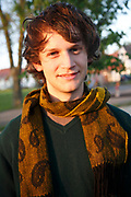 Portrait of young man looking straight at camera informal clothes brown hair and scarf