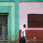Man walking past facade of old house in Trinidad, Cuba