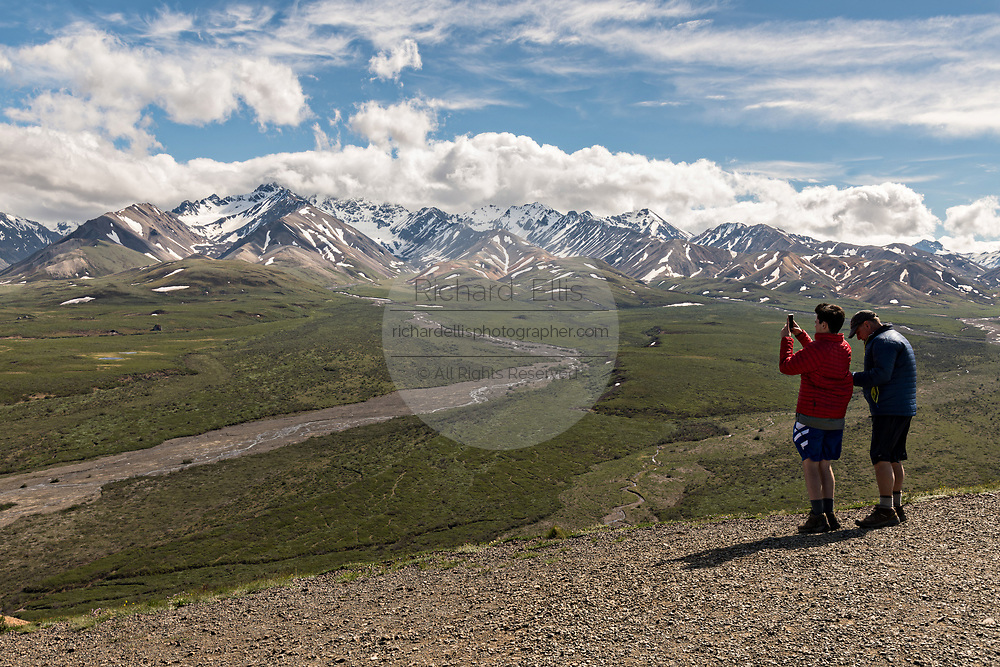Visitors take in the viiew of the Polychrome Hills and the Alaska Range alongside the Toklat River in Denali National Park Alaska. Denali National Park and Preserve encompasses 6 million acres of Alaska's interior wilderness.
