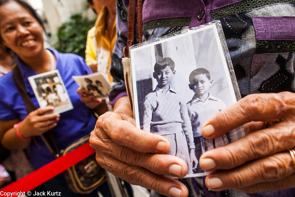 04 DECEMBER 2012 - BANGKOK, THAILAND: People hold pictures of Bhumibol Adulyadej, the King of Thailand, in the lobby of Siriraj Hospital. People pack the lobby of the hospital hoping the catch a glimpse of the King if he should make an unexpected visit to the lobby. He celebrates his 85th birthday Wednesday, Dec. 5. The King lives in Siriraj. He is expected to make a rare public appearance and address the nation from Mukkhadej balcony of the Ananta Samakhom Throne Hall in the Royal Plaza. The last time he did so was in 2006. His birthday is a public holiday in Thailand and hundreds of thousands of people are expected to jam the streets around the Royal Plaza and Grand Palace to participate in the festivities.    PHOTO BY JACK KURTZ