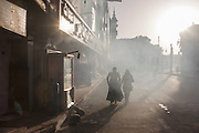 Two Egytptian women walk through smoky air, emitted from a kebab business on a street in Luxor, Nile Valley, Egypt.