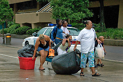 28th August, 2005. Hurricane Katrina, New Orleans, Louisiana. A family carry, drag, push and pull the few possessions they are able to take into the Superdome as thousands of people seek shelter inside therin just hours before devastating Hurricane Katrina hits the city.