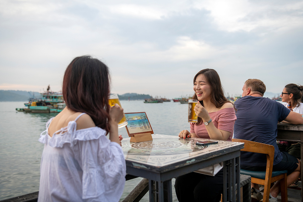 Two Korean tourists enjoy a glass of cold beer at the waterfront, a public walkway lined with restaurants, in Kota Kinabalu, Sabah, Malaysia. (August 9, 2019)
