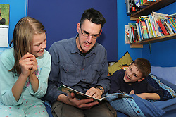 Father reading bedtime story to children UK
