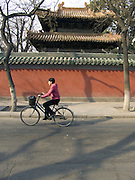 woman on a bicycle passing the old Lama temple complex China Beijing