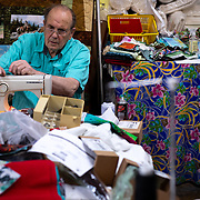 """Don Reiman (Town of Miami councilman) repairs a sewing machine, April 20, 2020, in Julie's Quilt Shop, Miami, Arizona. Julie's shop was considered an """"essential"""" business and remained open during the statewide stay-at-home order. Residents are cautious but not scared, Don says. The town is mostly locked down, even though there hasn't been one case of Covid-19 months into the crisis."""