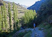 Woman walking River Rio Poqueira gorge valley, High Alpujarras, Sierra Nevada, Granada Province, Spain