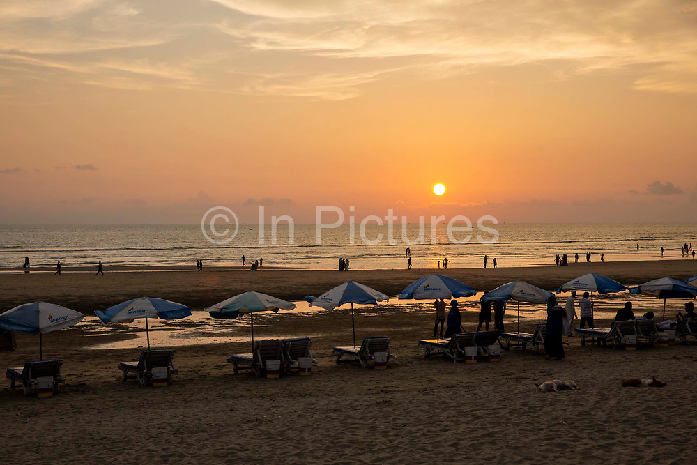 A row of sun-lounger beds and umbrellas at sunset on Laboni Beach looking out to the Bay of Bengal near in Cox Bazar, Chittagong Division, Bangladesh, Asia.  People stand around the sun-beds and others with two sleeping dogs, other people walk along the shoreline. This is part of the coastline which is claimed to be the longest natural sea sandy beach in the world, running 120 kilometers.