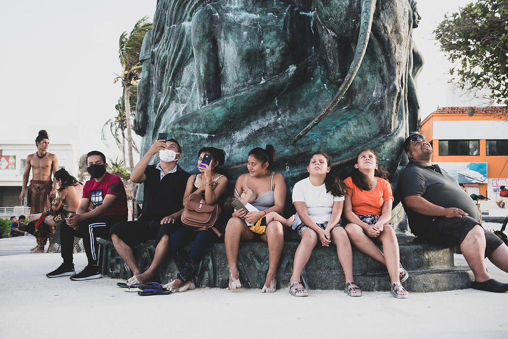 """Playa del Carmen, Mexico - May 25, 2021: Spectators sit at the base of the """"Portal Maya"""" sculpture at Parque Los Fundadores in Playa del Carmen, watching the ritual ceremony of the Papantla Flyers."""