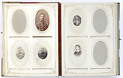 open vintage family photo album from late 1800s with portraits and missing photographs