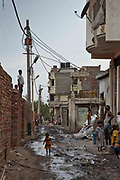 Tehkhand Slum, Delhi, India.  A young girl walks through a sewage river running through the slum that she lives in. Indian slums are characterized as a run-down area of a city with substandard housing, squalor and lacking in security.  They are home to increasing numbers of people and families who are usually very poor or socially disadvantaged. Most slums lack clean water, sanitation and other basic services, and as such they pose a serious threat to public health as infectious diseases are able to spread easily, such as Tuberculosis (TB) and cholera.
