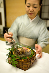 Woman in Kimono cooking traditional Japanese food in a Ryokan on Isu Pennisula in Japan