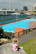 Child (6 years old) looking across Andrew (Boy) Charlton Swimming Pool. The Domain, Sydney, Australia