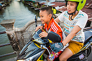 13 JANUARY 2013 - BANGKOK, THAILAND:  A woman and her son ride her motor scooter across Khlong Bang Luang in Bangkok. The Bang Luang neighborhood lines Khlong (Canal) Bang Luang in the Thonburi section of Bangkok on the west side of Chao Phraya River. It was established in the late 18th Century by King Taksin the Great after the Burmese sacked the Siamese capital of Ayutthaya. The neighborhood, like most of Thonburi, is relatively undeveloped and still criss crossed by the canals which once made Bangkok famous. It's now a popular day trip from central Bangkok and offers a glimpse into what the city used to be like.    PHOTO BY JACK KURTZ