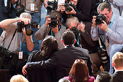 © Licensed to London News Pictures. 07/10/2012. Birmingham , UK . Baroness Sayeeda Warsi (left) with her husband Iftikhar Azam (right) with his arm around her shoulder (right) , surrounded by photographers as they take their seat ahead of the afternoon's speeches . Conservative Party Conference Day 1 at the International Convention Centre . Photo credit : Joel Goodman/LNP