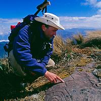 An  trekker looks at a Chachapoyan snake petroglyph atop Mount Shubet.