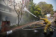 Luis Vargas, Los Angeles Fire Departmnet Class 1, Station 71, splashes the water to the house caught on fire on Wednesday, December 6th, 2017 at Casiano Boad in Bel Air, Los Angeles in California. (Photo by Yuki Iwamura)