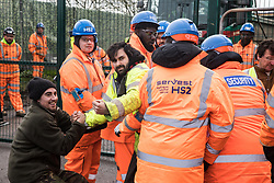 Harefield, UK. 8 February, 2020. HS2 engineers and security guards try to block environmental activists who had crawled through a ditch under a road closure implemented on Harvil Road in the Colne Valley to facilitate tree felling works for the high-speed rail project. Environmental activists based at a series of wildlife protection camps in the area prevented the tree felling works for the duration of the weekend for which they were scheduled.