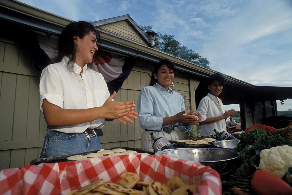 Three Hispanic women making gorditas at Hispanic cookout at a Texas Ranch.  Model Release.<br /> ©Bob Daemmrich