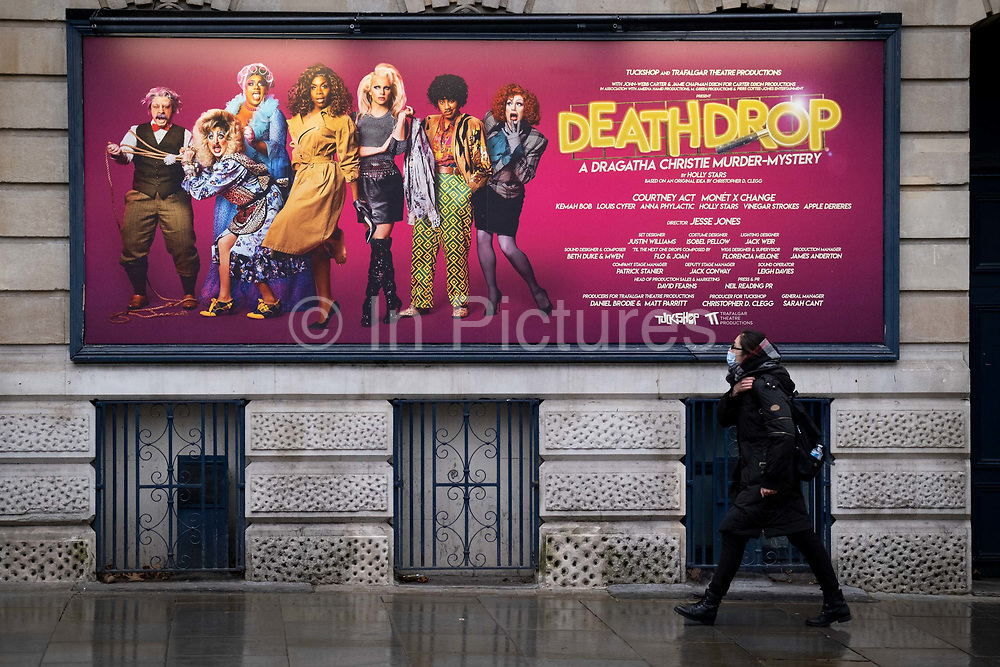 The day after the government introduced a third Coronavirus pandemic national lockdown, effectively a Tier 5 restriction, a masked woman walks beneath a West End theatre poster for the Agatha Christie murder mystery, Deathdrop, as the capital experiences a grim post-Christmas and millions of Britons are told to stay at home, on 5th January 2021, in London, England.