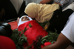 October 4, 2018 - Gaza - Relative kisses the forehead of Palestinian teen Ahmed Abu Habel, who was killed during a protest near the Israeli Erez crossing, during his funeral in the northern Gaza Strip. (Credit Image: © Majdi Fathi/NurPhoto/ZUMA Press)