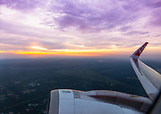Looking out the window of a commercial airliner with the engine and wing and a purple yellow sky and sun.  Air Asia on the wingtip. Editorial