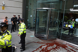 London, UK. 27th August, 2021. City of London Police arrest an environmental activist from Extinction Rebellion who spread fake blood outside the offices of law firm Debevoise & Plimpton LLP during a Blood Money March through the City of London. Extinction Rebellion were intending to highlight financial institutions funding fossil fuel projects, especially in the Global South, as well as law firms and institutions which facilitate them, whilst calling on the UK government to cease all new fossil fuel investment with immediate effect.