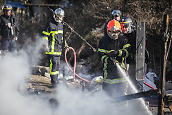 © London News Pictures. Calais, France. 04/03/16. Fire crews put out the smouldering remains of a shelter that was set on fire in the Calais 'Jungle'. French authorities are clearing the southern half of the Calais 'Jungle' camp, which charities estimate to contain 3,500 people.Photo credit: Rob Pinney/LNP
