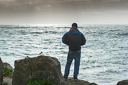 A man stands on Towan Headland in Newquay, Cornwall.