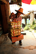 Woman carries dozens of eggs on her yoke in the area of Ping'an. Guangxi, China, Asia
