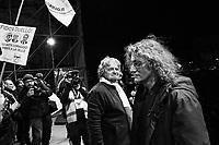 "ROME, ITALY - 22 FEBRUARY 2013: Comedian and leader of the Five Stars Movement Beppe Grillo (center) looks at the co-founder of the movement Gianroberto Casaleggio (right) as he walks towards the backstatge after giving a short speech during the closing rally for the general elections in Piazza San Giovanni, in Rome on February 22, 2013. Wrapping up his election campaign in Rome, Grillo said ""there are 800,000 thousand of you here - with 150,000 watching our live streaming, and 120 squares in Italy watching us"".<br /> <br /> Grillo, whom presents itself as a ""non-politician"", and the 5 Stars Movement as ""not a party"", has been running a mostly internet-based political campaign through the party's blog and the local groups that have emerged from it. The movement has a strong anti-politics agenda: ""All political parties are crooked and they all need to go"", Grillo says.<br /> <br /> <br /> A general election to determine the 630 members of the Chamber of Deputies and the 315 elective members of the Senate, the two houses of the Italian parliament, will take place on 24–25 February 2013. The main candidates running for Prime Minister are Pierluigi Bersani (leader of the centre-left coalition ""Italy. Common Good""), former PM Mario Monti (leader of the centrist coalition ""With Monti for Italy"") and former PM Silvio Berlusconi (leader of the centre-right coalition).<br /> <br /> ###<br /> <br /> ROMA, ITALIA - 22 FEBBRAIO 2013: Beppe Grillo, comico e leader del Movimento 5 Stelle (M5S), fa un comizio durante la tappa finale dello ""Tsunami Tour""  a Piaza San Giovanni, a Roma il 22 febbraio 2013. A conclusione del comizio, Beppe Grillo ha dichiarato: ""Siamo 800.000 e 150.000 in streaming, con 120 piazze collegate"".<br /> <br /> Grillo, il quale si presenta come un ""non-politica"", e il Movimento 5 Stelle come un ""non-partito"", svolge la maggior parte della propria campagna elettorale su internet, tramite il suo blog e i meetup locali. Il movimento ha un'agenda dalle connotazioni antipolitiche: ""I partiti sono finiti e i politici se ne de"