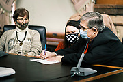 14 DECEMBER 2020 - DES MOINES, IOWA: CHARLIE JOHNSON, an at large Elector, corrects his ballot during the Electoral College vote. A member of the Secretary of State's legal staff (left, polka dot face mask) had a question about the way the ballot was marked. Iowa's six Electors met at the State Capitol Monday and voted for President Donald Trump and Vice President Mike Pence, cementing Trump's victory in Iowa. Trump carried Iowa by 8.2 percent in the November 3 general election.     PHOTO BY JACK KURTZ
