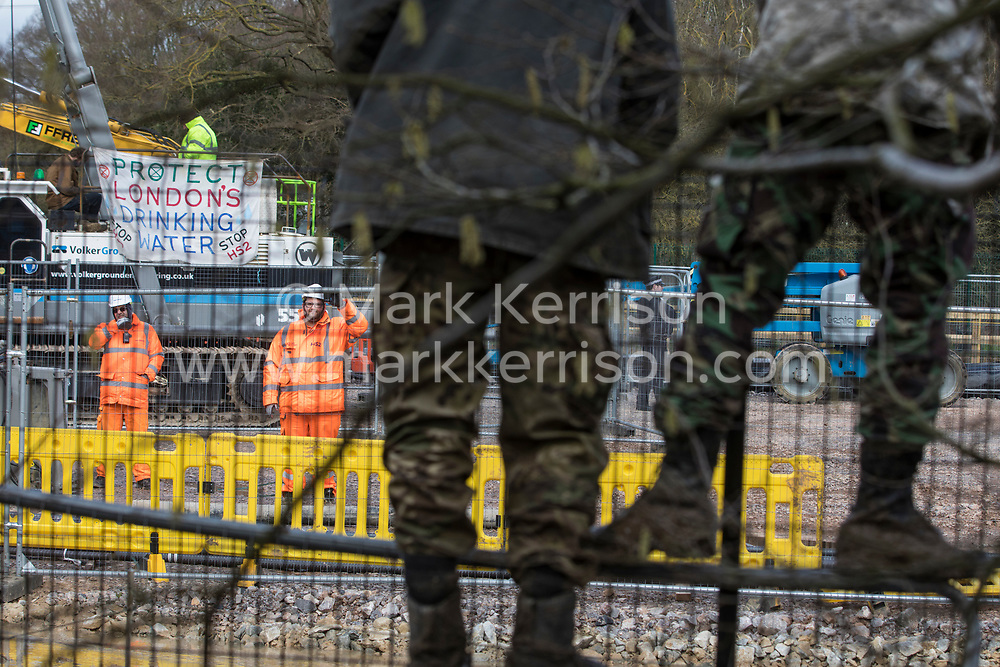 Harefield, UK. 18 February, 2020.  Environmental activists observe two Extinction Rebellion activists, including former Paralympic cyclist James Brown of Extinction Rebellion, who are locked onto a drilling rig, displaying a banner which reads: 'Protect London's drinking water. Stop HS2', at a site in the Colne Valley currently being used for the HS2 high-speed rail link. According to the activists from Stop HS2, Save the Colne Valley and Extinction Rebellion, HS2 are intending to use the rig to drill into the aquifer which supplies 22% of London's drinking water, risking contamination.