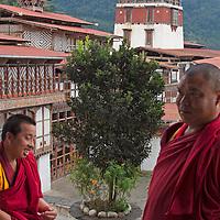Asia, Bhutan, Trongsa. Monks at Trongsa Dzong overlooking courtyard.