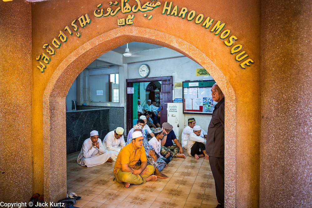 """08 AUGUST 2013 - BANGKOK, THAILAND:       Men pray in the entry way of Haroon Mosque during Eid al-Fitr in Bangkok. Eid al-Fitr is the """"festival of breaking of the fast,"""" it's also called the Lesser Eid. It's an important religious holiday celebrated by Muslims worldwide that marks the end of Ramadan, the Islamic holy month of fasting. The religious Eid is a single day and Muslims are not permitted to fast that day. The holiday celebrates the conclusion of the 29 or 30 days of dawn-to-sunset fasting during the entire month of Ramadan. This is a day when Muslims around the world show a common goal of unity. The date for the start of any lunar Hijri month varies based on the observation of new moon by local religious authorities, so the exact day of celebration varies by locality.   PHOTO BY JACK KURTZ"""