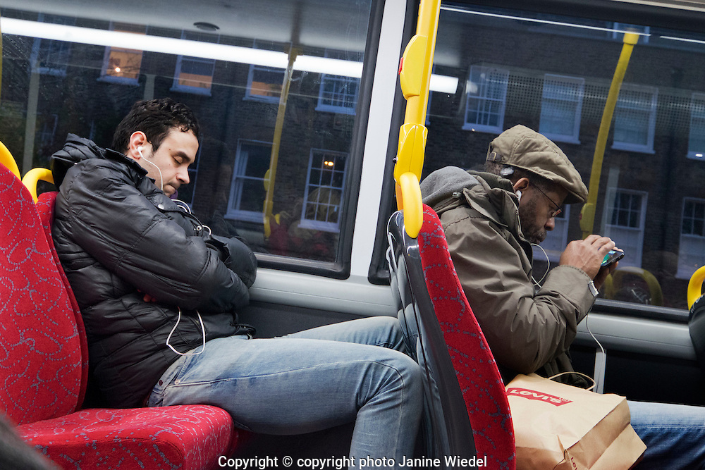 Two men listening to music on their phones on London bus