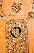 Ornate decorated wooden door with brass knocker in the old city, Ronda, Spain