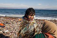 A young Afghan girl with her mother on a beach near the town of Molyvos, Lesvos island, Greece.
