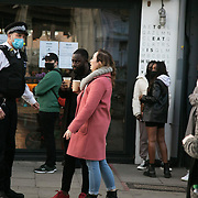Police asking people to move on in Broadway Market during the second coronavirus national lockdown on November 7th 2020 Hackney, East London, United Kingdom. The UK Government introduced a 4 week lockdown from November 5th - December 2nd to combat the corona virus outbreak. It is the second national lockdown in the UK. It is the third day of the national lockdown and the lockdown restrictions mean that people are only allowed to meet outside, in pairs and only if keeping social distance. Only if they already live together or have formed a social bubble can they interact freely.