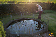 An elderly man checks the netting of his garden pond due to the visits of a local heron with an eye on his fish, on 5th May 2018, in Wrington, North Somerset, England.