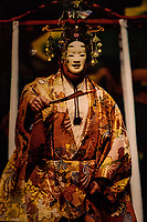 Noh theater involves music, dance and drama and themes are structured around song and dance. Movements are slow, the tone is monotonous  though the language is poetic and the costumes are rich and elaborate. Plots are usually drawn from legend, history, literature and contemporary events. Themes often relate to dreams, supernatural worlds, ghosts and spirits. Its origins are the 14th century and was developed together with kyogen - comical pieces performed during interludes of the main noh performance. The dual arts of noh and kyogen combined is known as nogaku - listed as an Intangible Cultural Heritage by UNESCO. Noh was popularized by Zeami during the Muromachi Period and attracted the government's patronage of the art form. Four main noh troupes were established, receiving sponsorship from shrines and temples.  During the Tokugawa Period the shogunate made noh its official ceremonial art and issued regulations for its governance. Noh thus became more standardized with an emphasis on tradition rather than innovation. A fifth troupe was added which have survived and perform even today.  Noh is performed on a square stage with all sides of the stage open, except for the back side which consists of a wall with a painted image of a pine tree.  One key element of noh are the masks which tell the audience what character is being portrayed:  demons, spirits, women and men of different ages. These masks are carved from blocks of Japanese cypress. The costumes have multiple layers and textures that create an effect of resplendence.  Fans are also used to express different objects such as lanterns or knives.