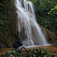 Hiker resting at Mae Sawan Noi Waterfall. located in Mae Hoh (or Mae Haw), Amphur Mae Sariang, Mae Hong Son, Thailand. This 5 tier waterfall is located in the hills close to Mae Sariang.