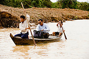 28 JUNE 2006 - CHONG KHNEAS, SIEM REAP, CAMBODIA: Students paddle their teacher to his school in Chong Khneas. The floating village of Chong Khneas is at the northwest end of Tonle Sap Lake, Cambodia's vast inland sea. More than 2,500 people live on the lake in houses that move as the lake expands and contracts with the seasons. During the dry season the lake covers about 2,500 square kilometers. At the peak of the rainy season the Tonle Sap swells to more than 13,000 square kilometers. Photo by Jack Kurtz / ZUMA Press
