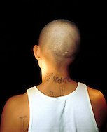 A street gang member in Fresno, California shows gang tattoos on his arm.