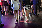 Young women are wearing high heels and short skirts are walking along Hollywood Boulevard during a night out in central Los Angeles, California, USA.